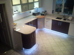 A high gloss white and plum kitchen with granite worktops