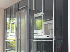 A wall filled with tall units in black gloss, housing two ovens, a microwave,a coffee machine and a large american fridge freezer
