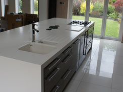 Another perspective of the corian wrapped central island showing the moulded sink and inlaid drainer