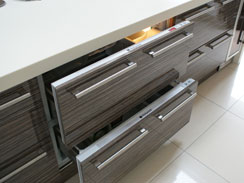 A close up of the built under fridge and freezer drawers