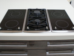 A close up of the twin gas hob sandwiched by two twin induction hobs